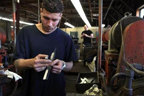 Eliseo Torres measures a blade after grinding.